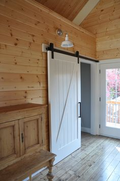 Farmhouse barn door painted white with black hardware. Looks great with the wood paneling on the walls and the white warehouse light mounted above. Love the door handle! - July 06 2019 at Interior Barn Door Hardware, Sliding Barn Door Hardware, Interior Doors, Sliding Doors, Interior Design, Wood Barn Door, Diy Barn Door, Indoor Door Handles, Barn Loft Apartment