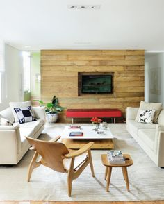 O piso laminado e o painel de madeira de demolição se encarregam de afirmar o estilo clássico do living que, em meio às cores quentes da chaise e das cadeiras, conferem um clima estiloso e moderno ao conjunto. Destaque para a poltrona de madeira com design de Sergio Rodrigues.