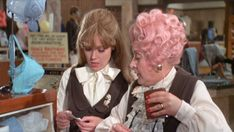 Miss Brahms (Wendy Richard) looks at the resulting photos as Mrs. Slocombe takes a stiff drink.