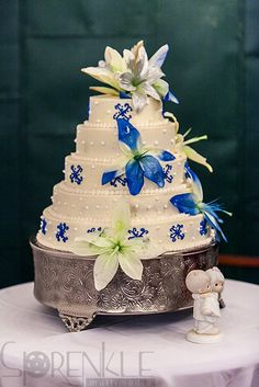 Wedding layer cake decorate with blue and white flowers with children figurine.