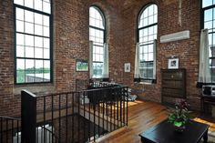 Exposed brick, tons of natural light, wood floors, and what looks to be a wrought iron spiral staircase. So, how soon can I move in?