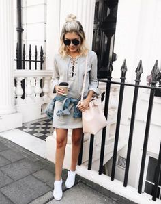 A lace-up sweater with a skirt, denim jacket, and sneakers.