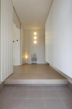 玄関ホールは、ヨーロピアンタイルを使用。クローゼットをはじめ白をベースにして、3つのブランケット照明が映えるセンスのいい空間に。クローゼットは、奥さまとお嬢さんの靴や傘などを考慮して、収納力がたっぷりあるものを選んだ。また、クローゼットは下部にLEDダウンライトが設置されており、ユニークな浮遊感を演出する
