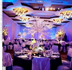 White fabric piping and drapery on the walls and white satin chair covers made the reception feel like a winter wonderland, while blue up-lighting gave the room an icy look.