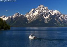 A boat sailing across Jackson Lake in Grand Teton National Park. The mountain on the distant shoreline is Mount Moran. With all of the breathtaking scenery here, it is definitely a must-see when visiting Grand Teton.