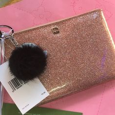 Kate spade gold rose clutch free pom pom keyring! New! Rose gold clutch with black leather holder. Comes with tags! Retails for 75! Free real rabbit pom pom keyring! $25 value! kate spade Bags Clutches & Wristlets