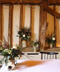 Earthenware pots filled with foliage for a barn wedding.