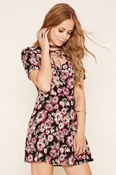 A woven dress featuring an allover floral print, slight A-line silhouette,short sleeves, self-tie front, a sweetheart neckline, and concealed side zipper.