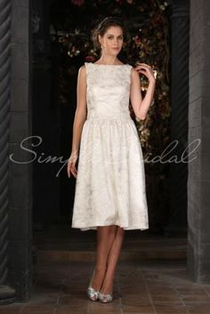 Wedding Dress by SimplyBridal. This vintage-inspired knee-length frock has Audrey Hepburn's favorite neckline, the bateau, which creates a lady-like and elegant appearance. The sleeveless style will draw attention to your neck, shoulders, and arms. The A-line silhouette is figure flatt. USD $279.99