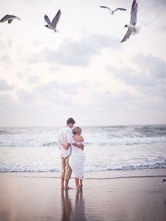 Pareja de novios mirando el mar quien ha sido testigo de su enlace