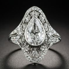 Few if any original Edwardian/Art Deco diamond rings come as fine and fabulous as this distinctive dazzler, hand fabricated in platinum - circa 1920s, starring none other than a blazing icy-white 1.36 carat European-cut pear shape diamond graded D color - Internally Flawless by the GIA. The gemmy diamond is presented in the rigorously detailed elegant manner in which it deserves. A glittering array of European-cut diamonds is accentuated with decorative hand piercing and fine milgraining.