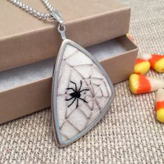 This unique silver asymmetrical triangular pendant necklace features a hand embroidered black spider on a light gray spider web on 100% pure white