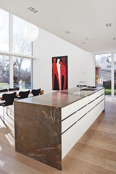 Køkkenet er bygget af en snedker, som er en bekendt af familien. De hvide og stramme linjer i rummet blødes op af trægulvet og den specielle bordplade i Pietra di Fossena-marmor