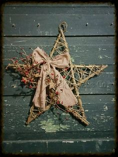 """A 10"""" twig mesh star is decorated with a homespun bow, berries, and a few rusty stars."""