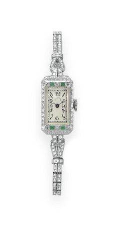 AN ART DECO DIAMOND AND EMERALD BRACELET-WATCH, BY TIFFANY & CO. With nickel-finished lever movement, 17 jewels, the rectangular cream dial with black Arabic numerals and hands, within a single-cut diamond and square-cut emerald bezel, to the openwork twin-row single-cut diamond articulated band, mounted in platinum, circa 1925, 6 ins., caseback with initials 'ACC' Dial signed Tiffany & Co., movement signed Concord Watch Co., caseback no. 44410