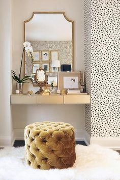 Glam vanity with gold accents, spotted wallpaper and a tufted velvet pouf.