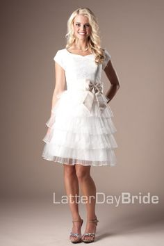 The Brendee   Short layered gown of pleated tulle with a taffeta bodice covered in tulle and lace appliques. A taffeta sash and bow finish this modest prom dress.    Available in Ivory w/ Champagne.    Dress Available at LatterDayBride.com or in Store At Latter Day Bride Located in Salt Lake City, Utah