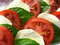 Caprese Salad: sliced fresh mozzarella, tomatoes and basil, seasoned with salt, and olive oil