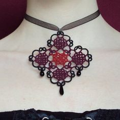 This dramatic choker is called Elizabeth Royale. It has been tatted in black, claret and red cotton thread and is part of my Frivolite Tudor Collection. The idea for this piece came from a small pattern I had created. I then added to it and this is the result.    One black glass flat drop hangs delicately from the base while two black glass teardrop beads hang either side of this. The motif is slightly under 3 1/4 inches (80mm) wide by 3 3/4 inches (96mm) long (including beads). By…