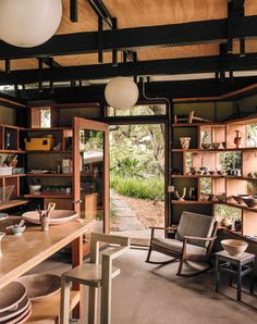 The ceramics studio was formerly a pergola wrapped in chicken wire, used as a dog kennel by the previous owner. Inside the new structure, a vintage Danish chair, found on eBay, provides a modern perch. The windows' deep mullions double as display shelves.