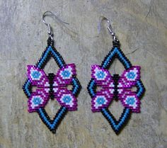 These pretty opened worked butterfly earrings are done in the brick stitch with size 11 delica glass beads. The colors that I have used are black, fuchsia, turquoise, lavender, and white. They measure 2 1/4 long. I do all of my own bead work one bead at a time. Thank you for looking at my bead work. Have a blessed day.