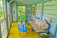Porch of house with painted wood floor, bright colors, rustic eclectic furniture rocker