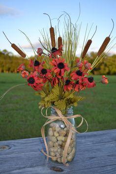 Fall floral arrangement using mason jar, fall flowers, cat tails, and fresh peanuts.