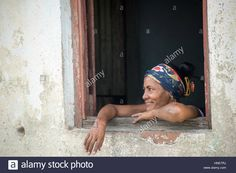 Download this stock image: Cuban woman looking outside from her house window. The Afro Caribbean lady stare the everyday life from her humble home. - hne7rj from Alamy's library of millions of high resolution stock photos, illustrations and vectors.