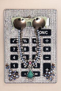 Inside Deputy Fashion Editor Anahita Moussavian's Closet: Green Reflective Sunglasses by Retro Superfuture, Earrings by Oscar de la Renta, Necklace by Dannijo, Bejeweled Calculator | coveteur.com