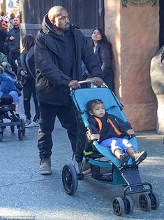 Daddy duty: The rapper pushed two-year-old North's stroller as they headed out of the park...