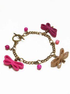 Pulsera con Charms  en tonos fuccia-rosados  de mariposas hechas a mano  en cinta rustica de algodon y antelina,  elaborada con cadena  en color bronce antiguo  y cuentas de colores.