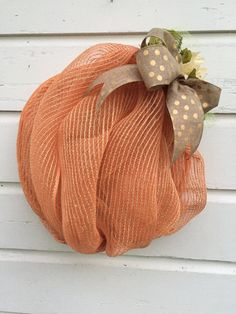 This beautiful pumpkin is ready to be hung on your porch or door for the fall season! Made of deco mesh and burlap, this pumpkin is durable and light, and can transition from Fall, to Halloween, on to the Thanksgiving holiday season.  Although suitable to hang indoors or out, this wreath will give you many more seasons of delight if hung protected from the elements. All of my wreaths come attached with a wired hanger loop for easy display.