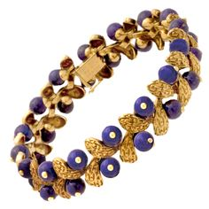 Van Cleef & Arpels. This bracelet from Van Cleef & Arpels showcases 2 rows of brilliant blue lapis lazuli beads interspersed with textured 18K gold abstracted leaf motifs.  France Ca. 1970s