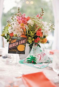 Brides Magazine: Unique Wedding Centerpieces - Ligustrum foliage, snapdragons, spray roses, stock, ranunculuses, solidagos, Queen Anne's lace, hydrangea florets, craspedia, and citrus fruit, accented with a vintage handkerchief and flamingo ornaments    Greenery Productions, Orlando, FL