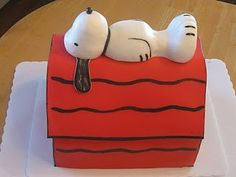Snoopy Birthday Cake - This cake was done for a little guy's Birthday - obviously a big Snoopy fan! I used two yellow sheet cakes with vanilla buttercream filling to cut and stack in the shape of Snoopy's dog house. I then covered the cake with a layer of buttercream, then red fondant. I used black food coloring mixed with lemon flavoring to paint the details on the dog house. Snoopy was hand formed using fondant. TFL!
