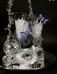 Photo about A shimmering silver mask trimmed with blue feather butterflies, a mirrored ball and champagne flutes filled with ice glass on silver party tray. Image of glass, mirror, shimmer - 21613137 Sweet 16 Masquerade, Masquerade Wedding, Masquerade Theme, Masquerade Ball Party, Masquerade Centerpieces, Mascarade Party Decorations, Wedding Centerpieces, Silver Party Decorations, Graduation Centerpiece