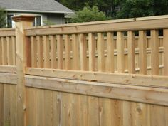 A tongue and groove natural cedar wood privacy fence, supported by large square posts with colonial style top caps and accented with a beautiful Essex topper. - Malone Fence Company Salem MA
