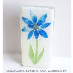 A personal favorite from my Etsy shop https://www.etsy.com/listing/157276938/blue-paper-decoupage-flower-on-glass-pin