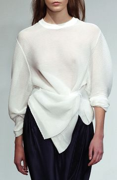 draped sweater with navy pleated skirt.
