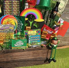 St. Patrick's Day raffle door prize basket What I used: wooden basket (Home Goods),dry floral foam (Amazon) Dollar Tree: giant pinwheel, Irish Spring, Leprechaun hat, foam shamrocks, lollipops, life savers, billion dollar bar Nobbies: Irish flag, green sprays, chocolate gold coins Hobby Lobby: starburst spray floral picks, leprechaun with dangly feet JoAnn: rainbow glasses Grocery Store: mini booze bottles, lottery tickets, snack size skittles, Andes mints