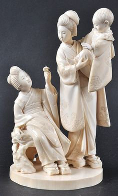 A 19TH CENTURY JAPANESE MEIJI PERIOD IVORY OKIMONO depicting two geishas, the standing geisha holding aloft a young child. 7.25in high
