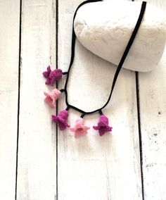Collar type crochet necklace with crochet lilac flowers with black beads. And suede leather are used to decorate the jewelry crocheted. It has a metal
