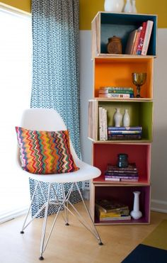 More wood crates are stacked for an bookcase. Painting the interiors of the crates a rainbow of bright hues relates to the bright colors downstairs and the Missoni-like pillows nearby. This is a fun and inexpensive solution for dressing up utilitarian crates.
