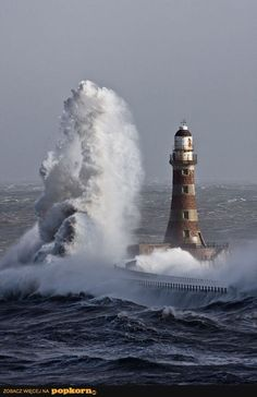 light house about to be hit by a wave
