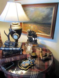 Love the unexpedness of plum plaid tablecloth with dark lamp base and other bits and bobs. (But they need to straighten the lampshade and the hanging picture.)