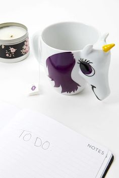 A ceramic mug by Thumbs Up™ featuring a unicorn design that changes color with hot water, a protruding face and horn, and a handle.