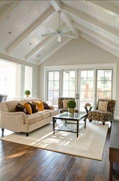 joli salon sous pente, tapis beige dans le salon. parquette foncé