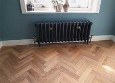 Our Aged Oak Parquet as fitted by Fin Wood. The natural colouring of the oak goes beautifully with the soft blue walls and dark radiator