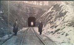 Real photo postcard with train in tunnel and railroad workers.