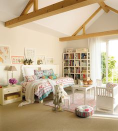 Amplio dormitorio infantil con mobiliario blanco y cuadros de dibujos en las paredes_00321052